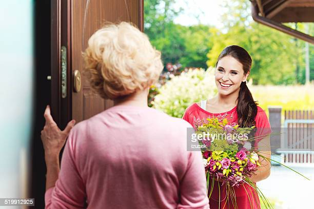 Young woman bringing birthday flowers to her grandmother