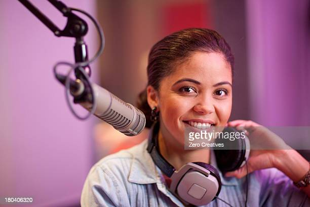 Young woman broadcasting in recording studio, portrait