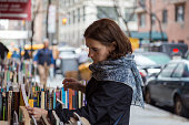 Young woman browsing books on the street
