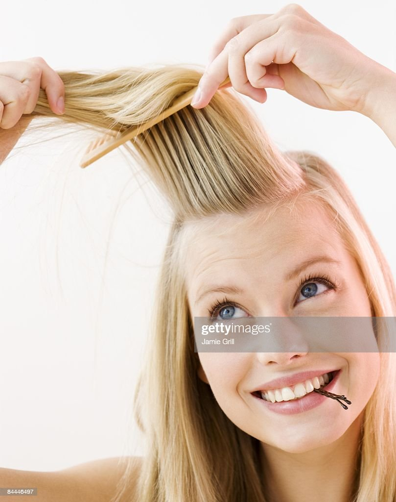 Young woman brushing and styling her hair : Stock Photo