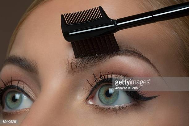 Young woman brushing eyebrows, close up.