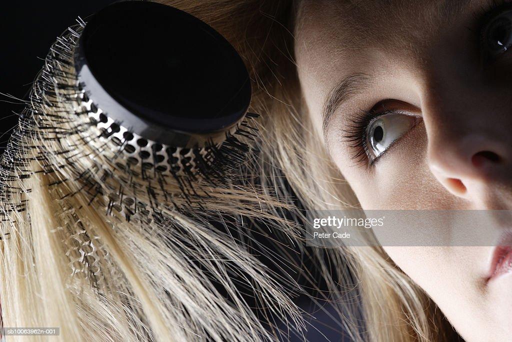 Young woman brushing hair, close-up