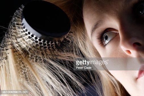 Young woman brushing hair, close-up : Stock Photo