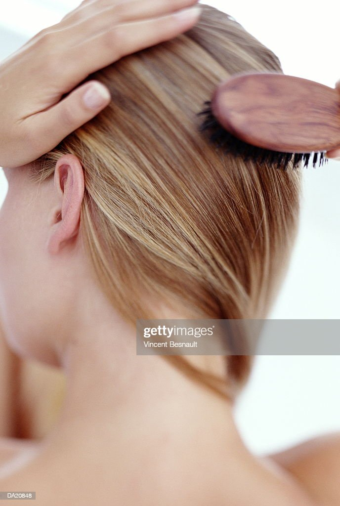 Young woman brushing hair, close-up, rear view : Stock Photo