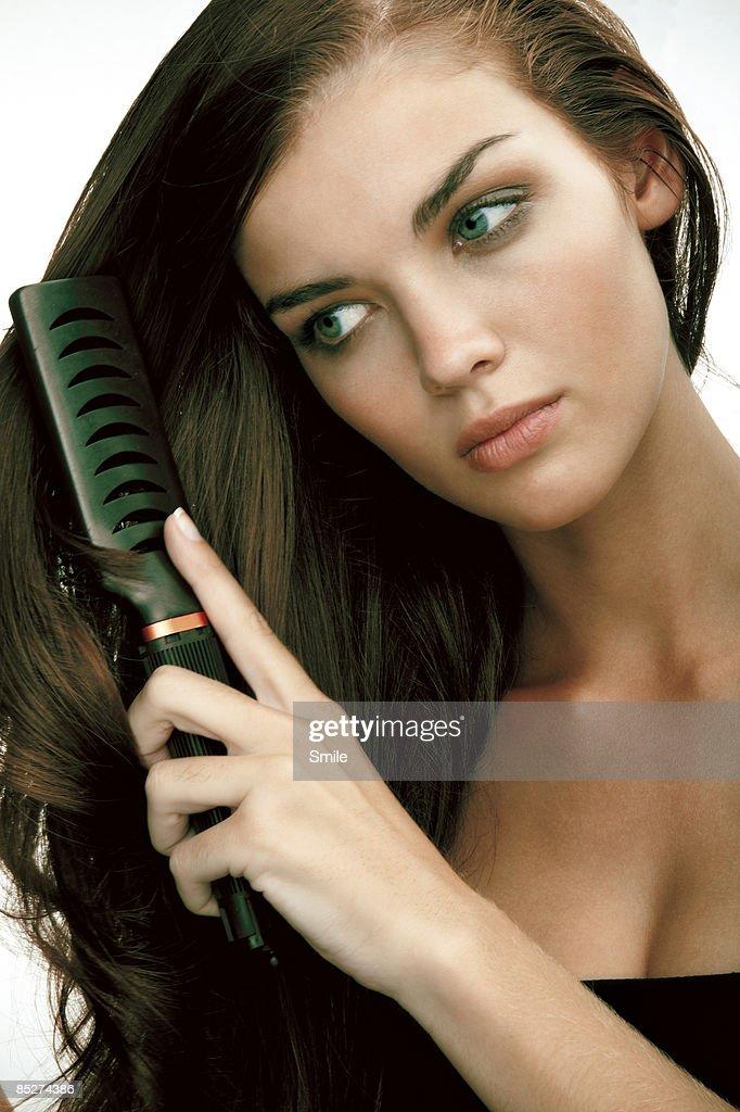 Young woman brushing hair