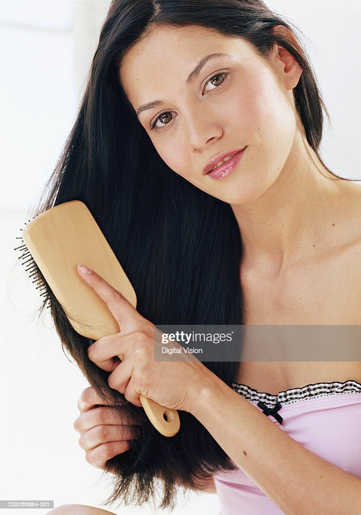 Young woman brushing hair, smiling, portrait