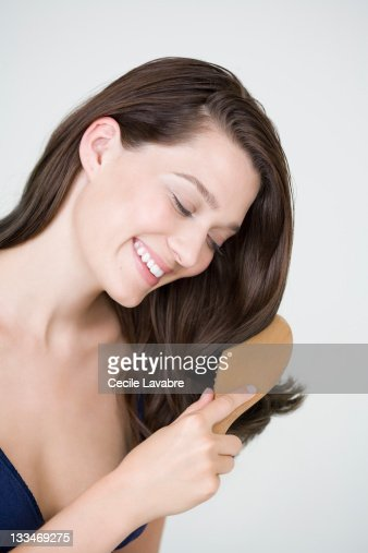 Young woman brushing her hair : Stock Photo