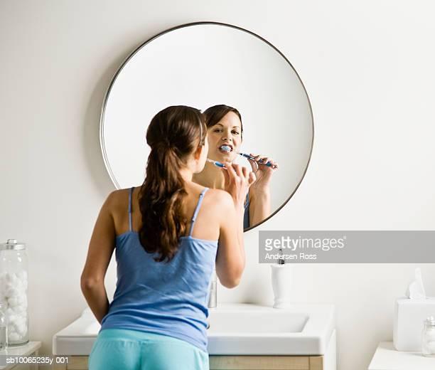 Young woman brushing teeth in bathroom, rear view