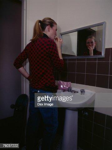 Young woman brushing teeth : Stock Photo