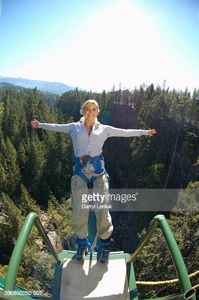 Young woman bungee jumping, smiling, portrait, (wide angle)