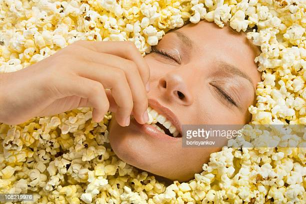 Young Woman Buried in Popcorn and Eating It