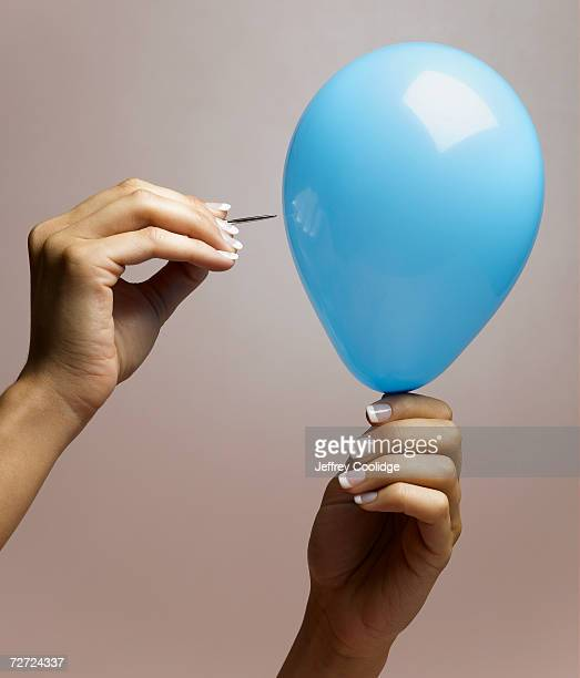 Young woman bursting balloon with pin, close up of hands