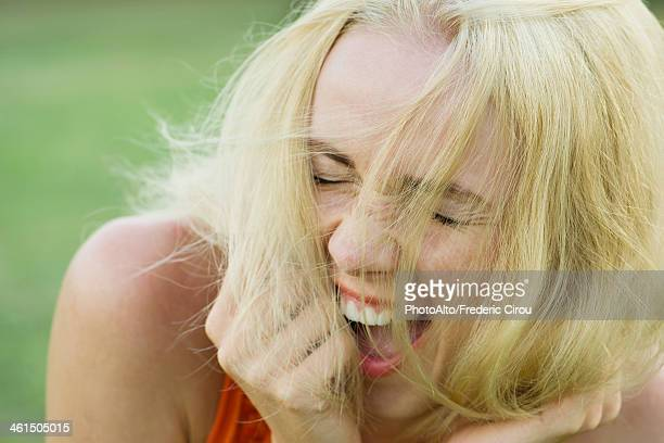 Young woman bursting out laughing with eyes closed