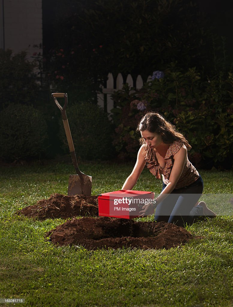 Young woman burying red box