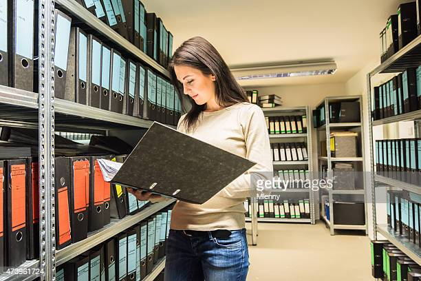 Young woman business accountant checking documents in finance file archive