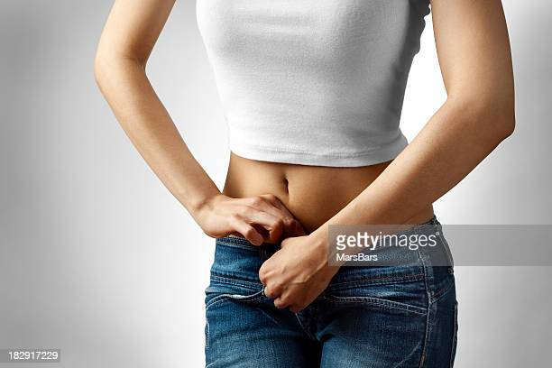 Young woman buttoning jeans - dieting concept