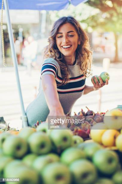 Jeune femme achat de pommes