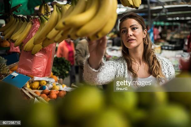 Young woman buying bananas at farmer's market.