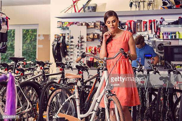 Young woman buying bicycle