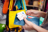 Young woman buying handbag, San Lorenzo market, Florence, Tuscany, Italy