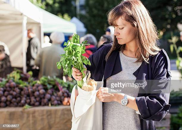 Young woman buying leaf vegetables at market