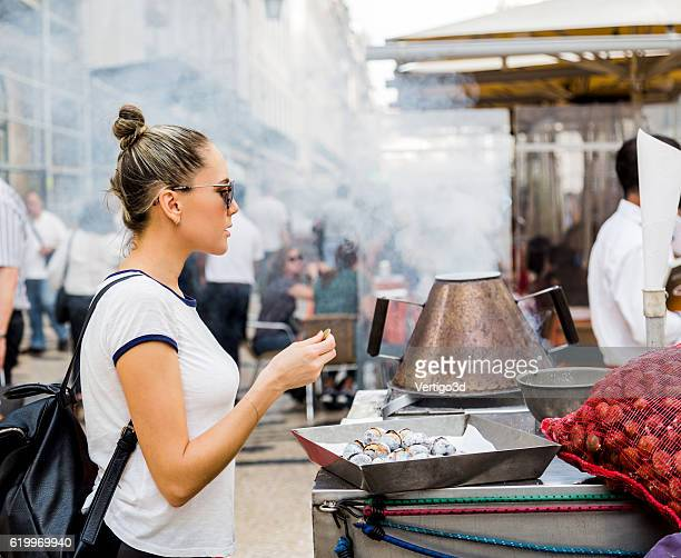 Young woman buys chestnut on the Lisbon street