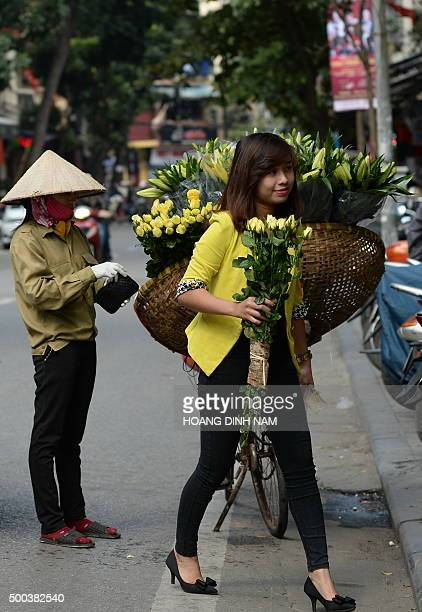 A young woman buys yellow roses from a street vendor in the Old Quarter of Hanoi on December 8 2015 AFP PHOTO / HOANG DINH NAM / AFP / HOANG DINH NAM