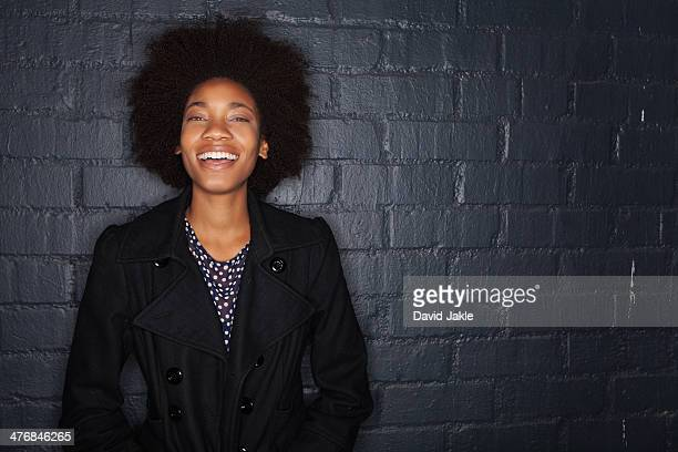 Young woman by black brick wall wearing black jacket