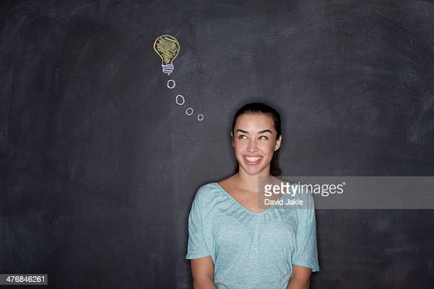Young woman by blackboard with lightbulb