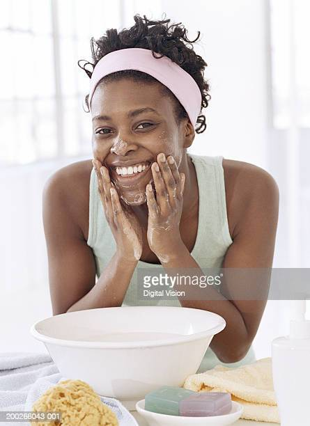 Young woman by bowl, washing face with soap, smiling, portrait