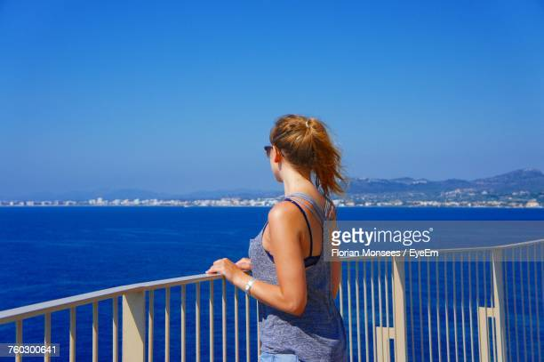 Young Woman By Railing Looking At Sea On Sunny Day