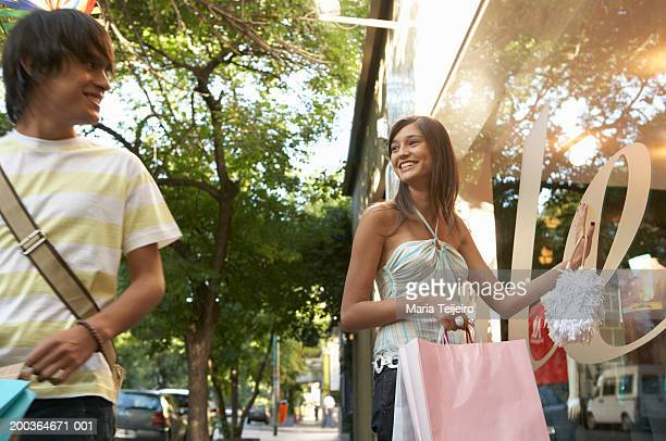 Young woman by shop window, smiling at teenage boy (16-18)