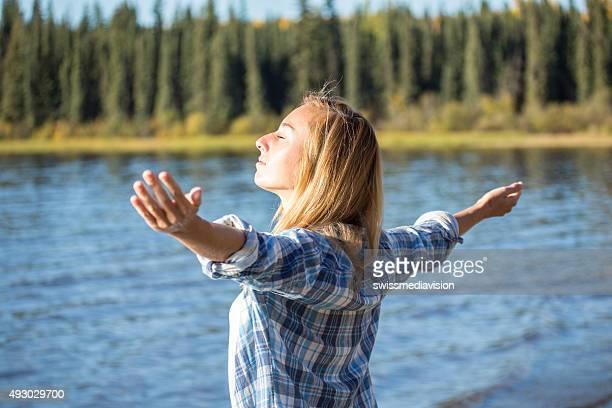 Junge Frau am See Ausgestreckte Arme