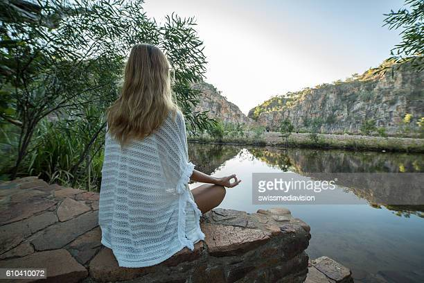 Young woman by the lake exercises yoga in lotus position