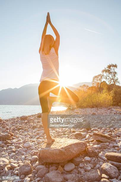 Young woman by the lake exercising yoga at sunrise