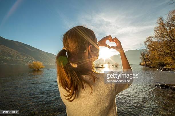 Jeune femme sur le lac en forme de cœur Cadrage avec les doigts