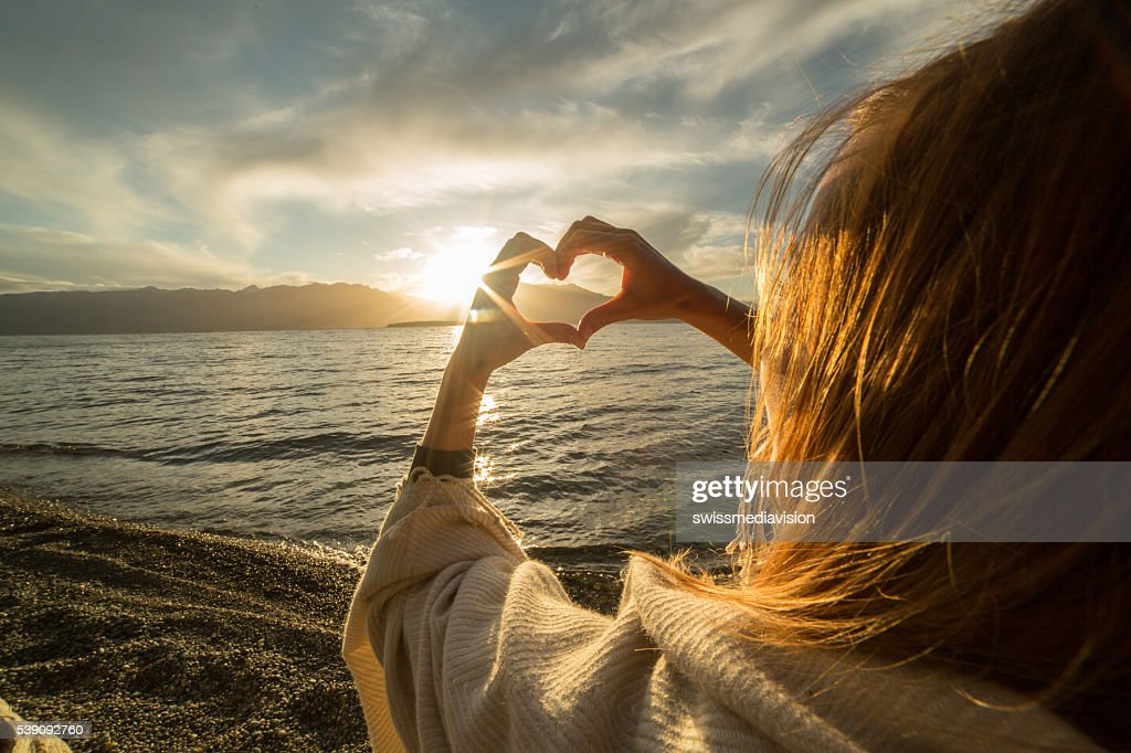 Young woman by the lake making heart shape finger frame