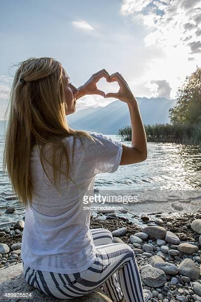 Junge Frau am See machen Herzform mit Händen