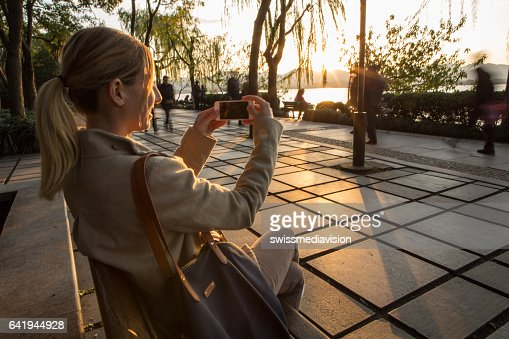 Young woman by the lake using mobile phone