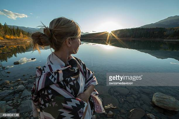 Young woman by the lake watching the sunset.