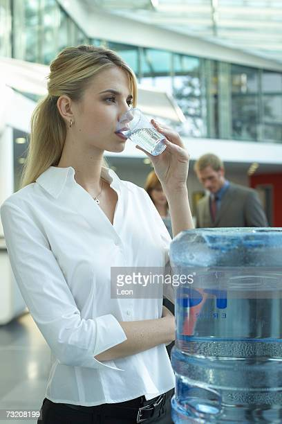 Young woman by water cooler in office