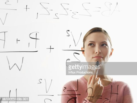 Young woman calculating equations on glass : Stock Photo