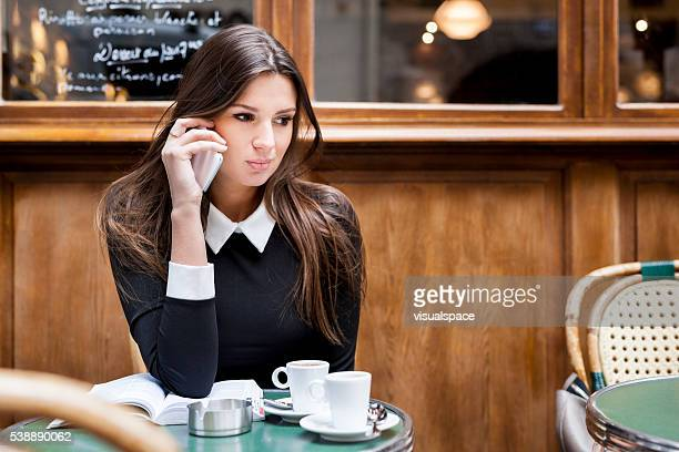 Young Woman Calling A Friend While Relaxing In A Cafeteria