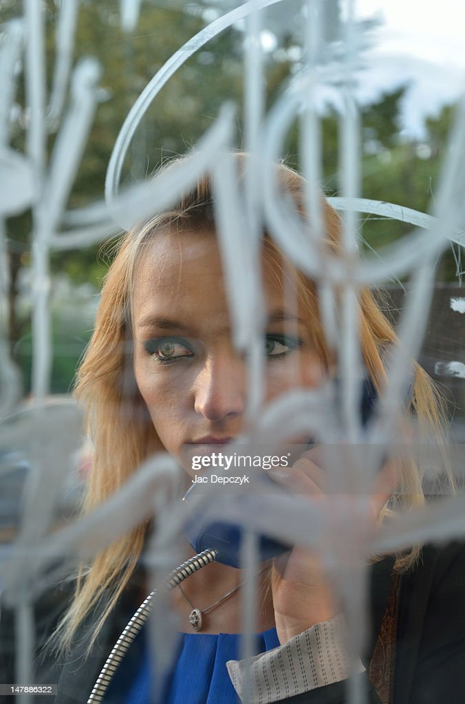 Young woman calling in a graffiti'd phone box : Stock Photo