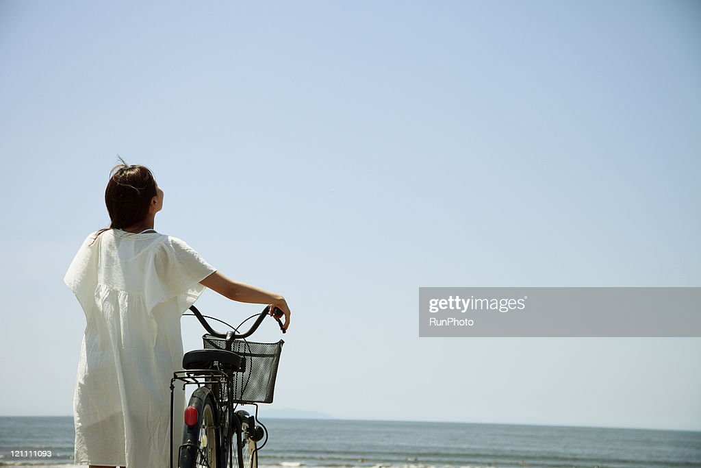 young woman came to the beach by bicycle : Stock Photo