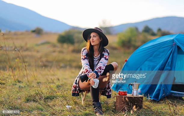 Young woman camping and drinking coffee