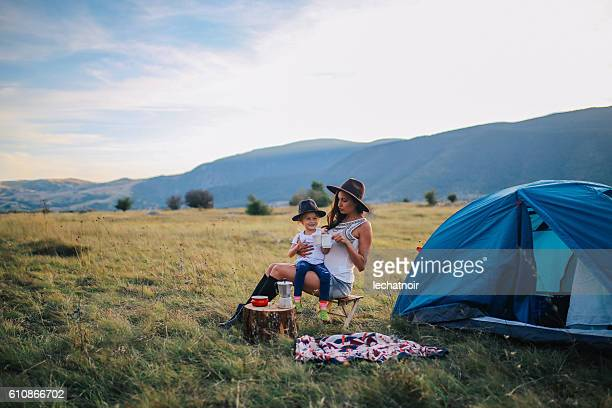 Young woman camping with a baby girl