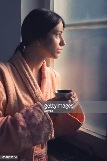 病院の窓の横にあるコーヒーを飲む若い女性がん患者