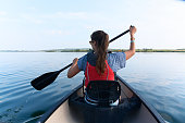 Young lady with long straight brunette hair in sunglasses and life vest paddling the kayak, canoeing in the lake on a summer sunny day on blue sky background. Vacation, sport, hobby.