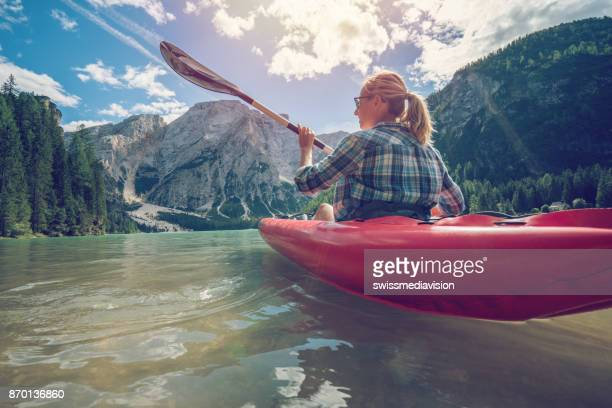Young woman canoeing on lake Braies, Italy